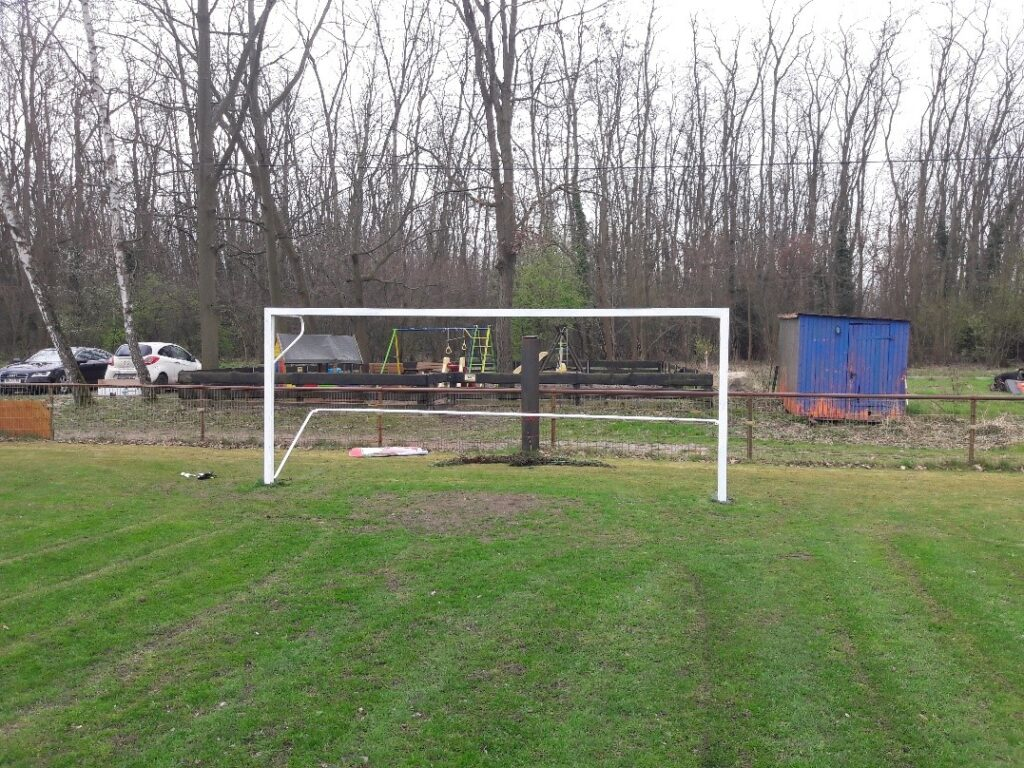 Bild, das im Vordergrund das Tor des Kleinfeldspielplatzes zeigt und im Hintergrund der Spielplatz zu sehen ist.